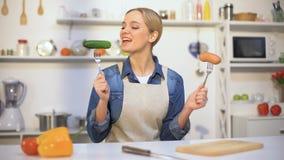 Ragazza graziosa che sceglie la salsiccia del cetriolo invece, alimento ipocalorico contro i carboidrati archivi video