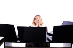Ragazza graziosa che si siede ad una tavola davanti a molti computer portatili isolati Fotografia Stock