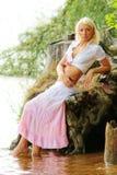 Ragazza graziosa che si siede al puntello del lago fotografia stock libera da diritti