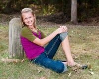 Ragazza graziosa che si siede all'aperto Fotografie Stock