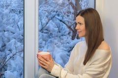 Ragazza graziosa che si siede sul davanzale, guardante la finestra e bevente tè Inverno all'esterno Immagini Stock