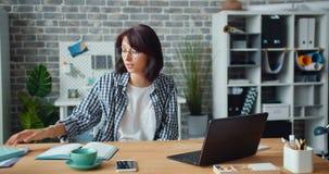 Ragazza graziosa che skyping nell'ufficio che parla esaminando lo schermo del computer portatile che gesturing sul lavoro archivi video
