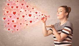Ragazza graziosa che soffia i simboli rossi del cuore Fotografia Stock Libera da Diritti