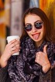 Ragazza graziosa che sta davanti alla parete con la tazza di caffè Fotografie Stock Libere da Diritti