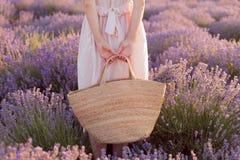 Ragazza graziosa che sta nel cappello d'uso della fedora del giacimento della lavanda con la grande borsa in sua mano immagine stock libera da diritti