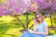 Ragazza graziosa che studia con il computer portatile e le carte in parco Fotografia Stock