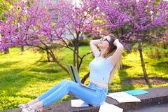 Ragazza graziosa che studia con il computer portatile e le carte, riposanti nel parco Fotografia Stock