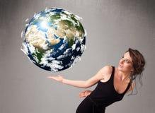 Ragazza graziosa che tiene la terra del pianeta 3d Immagini Stock