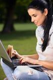 Ragazza graziosa che utilizza computer portatile nella sosta Immagini Stock Libere da Diritti