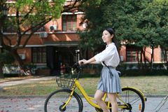 Ragazza graziosa cinese asiatica felice che guida un vestito dello studente di usura della bici a scuola Fotografie Stock Libere da Diritti