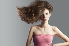 Ragazza graziosa con grande stile di capelli. Fotografia Stock