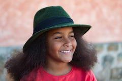 Ragazza graziosa con i capelli lunghi di afro con un black hat elegante Immagini Stock Libere da Diritti