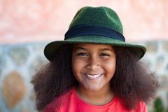 Ragazza graziosa con i capelli lunghi di afro con un black hat elegante Immagini Stock