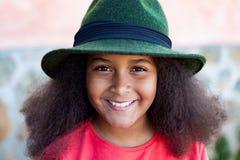 Ragazza graziosa con i capelli lunghi di afro con un black hat elegante Fotografia Stock Libera da Diritti