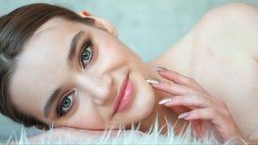 Ragazza graziosa con i grandi occhi della pelle pulita e le sopracciglia scure che esaminano macchina fotografica Concetto del pr stock footage