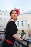 Ragazza graziosa con il fiore sul balcone esterno Fotografie Stock