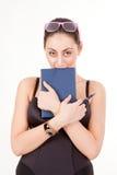 Ragazza graziosa con il libro, la penna ed i vetri Fotografia Stock