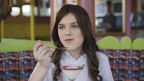 Ragazza graziosa con il sorriso che mangia dessert saporito in caffè 4K archivi video