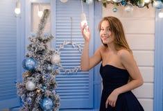 Ragazza graziosa con lo smillig lungo dei capelli vicino all'albero di Natale Fotografie Stock Libere da Diritti
