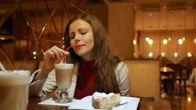 Ragazza graziosa con un latte del caffè in un caffè Una ragazza si siede in un caffè con un latte in un vetro video d archivio