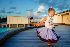 Ragazza graziosa del bambino in pannello esterno del tutu al tramonto fotografia stock
