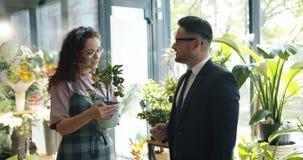 Ragazza graziosa del fiorista che vende pianta esotica all'uomo di mezza età nel deposito di fiore video d archivio
