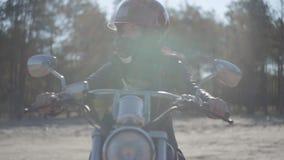 Ragazza graziosa del ritratto che indossa casco nero che si siede sul distogliere lo sguardo del motociclo Hobby, viaggiare e sti video d archivio