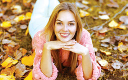 Ragazza graziosa del ritratto di autunno che si trova sulle foglie Immagine Stock