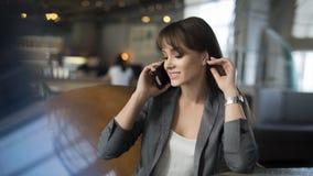 Ragazza graziosa del ritratto sulla poltrona in appartamento moderno di mattina Parla il telefono cellulare e sembra soddisfatta immagine stock libera da diritti