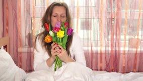 Ragazza graziosa della donna con i tulipani variopinti ed esaminare macchina fotografica ed odorare fiore archivi video