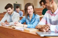Ragazza graziosa dello studente che parla con groupmate alla classe Fotografia Stock Libera da Diritti