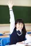 Ragazza graziosa dello studente che solleva mano in aula Immagini Stock