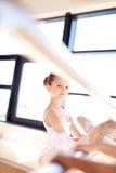 Ragazza graziosa di balletto che allunga la sua gamba facendo uso di Antivari Fotografia Stock