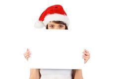 Ragazza graziosa di Santa che sorride alla macchina fotografica con il manifesto Immagine Stock
