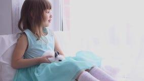 Ragazza graziosa divertendosi, abbracciando e giocando con il coniglio decorativo video d archivio