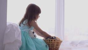 Ragazza graziosa divertendosi, abbracciando e giocando con il coniglio decorativo stock footage