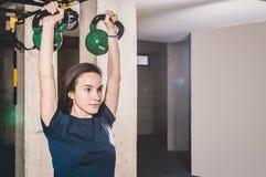 Ragazza graziosa e bella che tiene due campane del bollitore in sue mani per forza e che condiziona allenamento nella palestra, s Fotografie Stock
