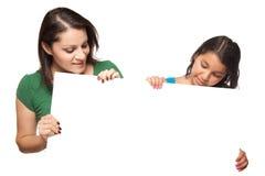 Ragazza graziosa e madre ispanice che tengono verro in bianco Fotografia Stock Libera da Diritti