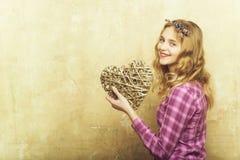Ragazza graziosa felice con cuore di vimini per il giorno di biglietti di S. Valentino fotografie stock