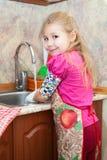 Ragazza graziosa nei piatti di lavaggio della cucina Immagini Stock Libere da Diritti