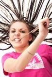 Ragazza graziosa nel colore rosa che morde i suoi capelli immagine stock