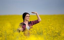 Ragazza graziosa nel giacimento giallo del seme di ravizzone fotografia stock