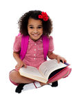 Ragazza graziosa sorridente della scuola che legge un libro Fotografie Stock Libere da Diritti