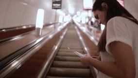 Ragazza graziosa in sottopassaggio Giovane donna castana in una maglietta bianca su una scala mobile che si alza stock footage