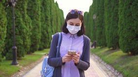 Ragazza graziosa in una maschera medica protettiva sul suo fronte nel parco facendo uso del telefono video d archivio