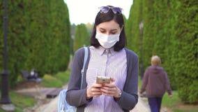 Ragazza graziosa in una maschera medica protettiva sul suo fronte nel parco facendo uso del telefono, Mo lento archivi video