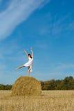 Ragazza graziosa in vestito bianco sul mucchio di fieno nel campo   Fotografia Stock Libera da Diritti
