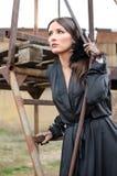 Ragazza graziosa in vestito nero elegante che sta sull'armatura Fotografie Stock Libere da Diritti