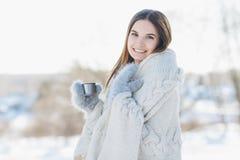 Ragazza in guanti e una coperta che bevono tè caldo Fotografie Stock Libere da Diritti