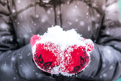 Ragazza in guanto rosso che tiene una manciata di neve Fotografia Stock Libera da Diritti